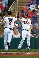 Minnesota Twins third baseman Trevor Plouffe (24) high fives Joe Mauer (7) after scoring a run during a Spring Training game against the Boston Red Sox on March 16, 2016 at Hammond Stadium in Fort Myers, Florida.  Minnesota defeated Boston 9-4.  (Mike Janes/Four Seam Images)