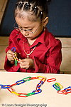 Education Preschool 3-5 year olds girl with serious expression putting together colored plastic links into a chain vertical