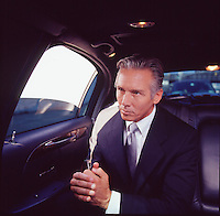 Man in suit in back seat of limousine