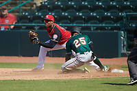 Fabricio Macias (25) of the Greensboro Grasshoppers slides into first base as Curtis Terry (29) of the Hickory Crawdads waits for the throw as umpire Josh Gilreath looks on at L.P. Frans Stadium on May 26, 2019 in Hickory, North Carolina. The Crawdads defeated the Grasshoppers 10-8. (Brian Westerholt/Four Seam Images)