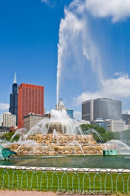Chicago's Buckingham Fountain shoots high over the skyline on a blue sky day
