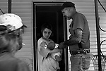 """Evangelist Gene """"Bones"""" Boswell says a blessing over 2-week-old Autumn Raines, held by mother Christine Gravely, in front of Gravely's home in Burlington.  The baby, born with a cleft lip and palate, will have her first surgery in August.  """"I meet people where they are, out on these streets and inside these neighborhoods,"""" said Boswell.  """"That's where God met me."""""""