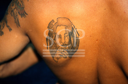 Salvador, Bahia State, Brazil; man with tattoo of Bob Marley on his shoulder.