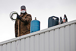 © Hughes Léglise-Bataille/Wostok Press.02.04.2010.Un salarié de Sodimatex  sur le toit de l'usine de Crépy-en-Valois le 02/04/2010 brandit les cables électriques reliés à une citerne de gaz en contrebas, à côté de cocktails molotov et d'une bonbonne de gaz. Retranchés dans leur usine depuis 24h, ils menacent de faire exploser une citerne de gaz, tandis que des négociations ont repris avec la direction, le maire, et le préfet de l'Oise. Les 92 salariés du fabricant de moquette pour l'automobile, dont la fermeture de l'usine a été programmée depuis 1 an, réclament un meilleur plan social.