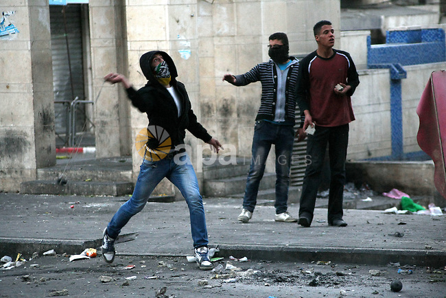 Palestinians throw stones at Israeli soldiers during clashes in the West Bank city of Hebron, 13 March 2013, following the funeral of Mahmoud Adel al-Titi, 22, who was shot dead by an Israeli soldier during an Israeli military operation in al-Fawwar refugee camp on Tuesday. Photo by Mamoun Wazwaz