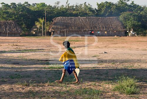 Mato Grosso State, Brazil. Aldeia Metuktire. Child in the village with Brazilian flag draped around the shoulders.
