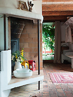 The large brick stove in the kitchen is one of the modern additions to the house, providing not only heat, it also functions as a room divider