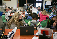 Kim Crawford, kindergarten teacher, (from left) helps Ian Lopez with an assignment, Monday, October 5, 2020 at Clinton Elementary School in Clinton. Check out nwaonline.com/2010010Daily/ for today's photo gallery. <br /> (NWA Democrat-Gazette/Charlie Kaijo)