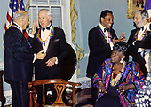 """The recipients of the 16th Annual Kennedy Center Honors share an informal moment as they pose for a group photo following a dinner at the United States Department of State in Washington, D.C. on Saturday, December 4, 1993.  From left to right: conductor Georg Solti, former """"Tonight Show"""" host Johnny Carson, Arthur Mitchell, founder of the Dance Theatre of Harlem, gospel singer Marion Williams and and composer and lyricist Stephen Sondheim.  The 1993 honorees are: Johnny Carson, Arthur Mitchell, Georg Solti Stephen Sondheim and Marion Williams.<br /> Credit: Greg E. Mathieson / Pool via CNP"""