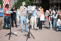 """People talk on a bullhorn as Wayfair employees demonstrate in Copley Square to protest their company's sale of furniture to detainment camps for children operated by US Customs & Border Protection (CBP) on the Mexico border in Boston, Massachusetts, USA, on Wed., June 26, 2019. Wayfair is an online furniture retailer. Employees are asking for the company to set ethics standards for sales. The Wayfair employees were joined by union representatives, PRIDE activists, and other groups in solidarity.  This action occurred the week after US government legal representatives argued that children held in CBP facilities did not need soap or beds to meet the """"safe and sanitary"""" standard of care required by law after months and years of criticism of Trump administration policies of family separation and cruel treatment of those held at its facilities."""