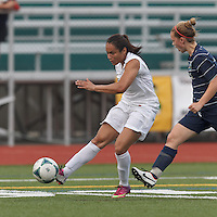 Boston Aztec forward Sonia Basma (8) crosses the ball.  In a Women's Premier Soccer League (WPSL) match, Boston Aztec (white) defeated Seacoast United Phantoms (blue), 3-0, at North Reading High School Stadium on Arthur J. Kenney Athletic Field on on June 25, 2013.