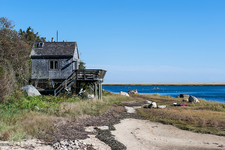 Quaint beach cottage on stilts with rowboat along Weeset Point, Nauset Harbor, Cape Cod, MA