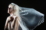 Woman wrapped in plastic viel, saintly pose, looking for the light.