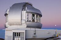 Gemini Northern 8-meter telescope, Mauna Kea Observatory seen at sunset, with the moon rising behind.