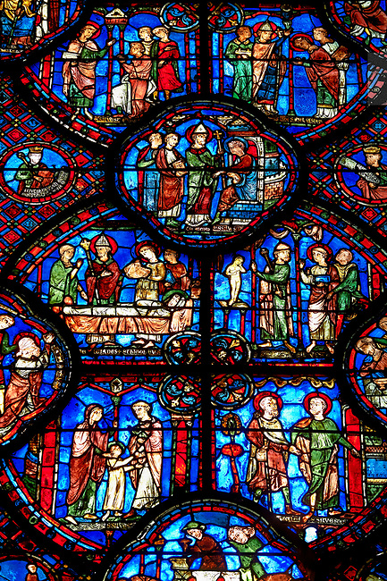 Medieval stained glass Window of the Gothic Cathedral of Chartres, France - dedicated to St Sylvester.  Bottom left - The young Sylvester presented by his mother to the priest Cyrinus, bottom right - Sylvester welcoming St Timothy to his house. Side panel right - above right - Execution of St Timothy , side panel left - Death of the prefect Tarquin, who chokes on a fish bone. Two centre panels, left- Funeral of St Timothy, right - Sylvester refusing the prefect's orders to worship an idol. Top central oval panel - Sylvester released from prison by Pope Melchiades. Above left - People beg Sylvester (holding book) to become a deacon, above right - Sylvester is ordained by Melchiades as deacon. A UNESCO World Heritage Site.