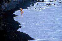 A woman walks on the edge of a black sand beach on Maui.
