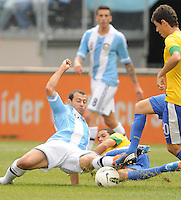 Argentina defender Javier Mascherano (14) goes down to save a play from Brazil midfielder Oscar (10) The Argentina National Team defeated Brazil 4-3 at MetLife Stadium, Saturday July 9 , 2012.