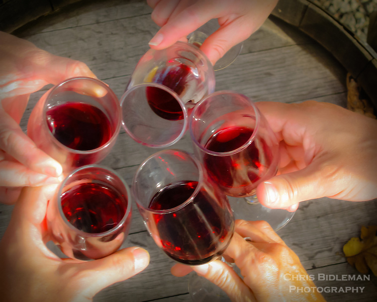 Five friends toasting wine glasses over a wine barrel as viewed from above with only hands and wine glasses seen.