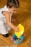Ten month old baby girl looking for and finding hidden toy, lifting top off plastic toy pot