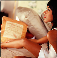 African American woman relaxing amoungst pillows<br />