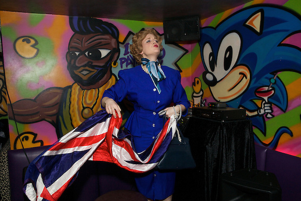 Margaret Thatcher impersonator Honey Wilde waves a Union flag before performing a strip tease at Maggies Nightclub in Chelsea