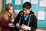 High school students checking phones in corridor.