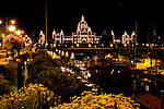 Night view of the British Columbia Parliament from the city of Victoria Visitor Center looks down the promenade past street artists, yachts, and the inner harbor.