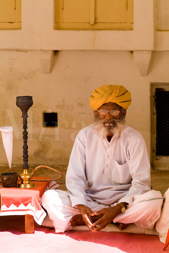 Jodhpur at Fort Mehrangarh in Rajasthan. India Hindu  man with water pipe at  doorway of Fort Palace.