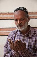 Agra, India.  Altaf Hussein, Caretaker of the Jama Masjid, the Friday Mosque, Praying.