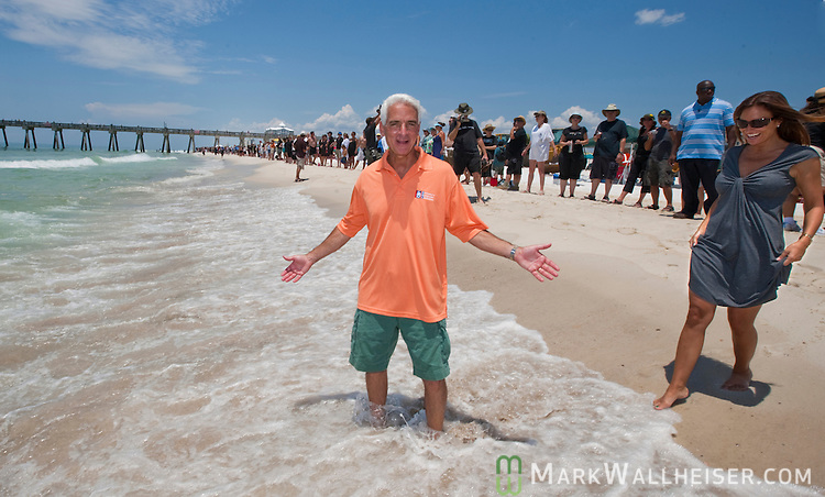 Florida Governor Charlie Crist and his wife Carole join several hundred people as they line Pensacola Beach for the Hands Across the Sand protest against offshore oil drilling in Pensacola Beach, Florida June 25, 2010.