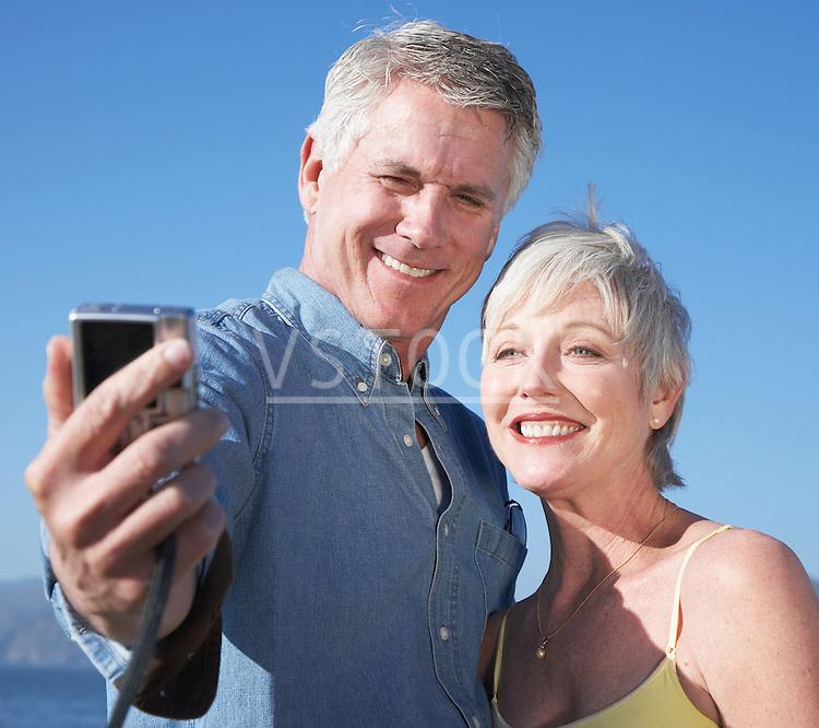 USA, California, Fairfax, Mature couple photographing self against blue sky