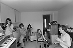 Moving into new home, family with teenage children and younger exhausted sitting in kitchen having a snack, after the removal men have left. 1977. New town Milton Keynes Buckinghamshire 1970s UK