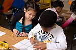 Education Elementary Grade 3 boy and girl playing math board game created by students