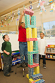 MR / Schenectady, NY. Zoller Elementary School (urban public school). Kindergarten inclusion classroom. Students build tall structure using large cardboard blocks at free playtime. Boy left: 5; boy center: 5, bi-racial; boy right: 6, African American & Puerto Rican American. MR: Gia3, Was3, Car38. ID: AM-gKw. © Ellen B. Senisi.