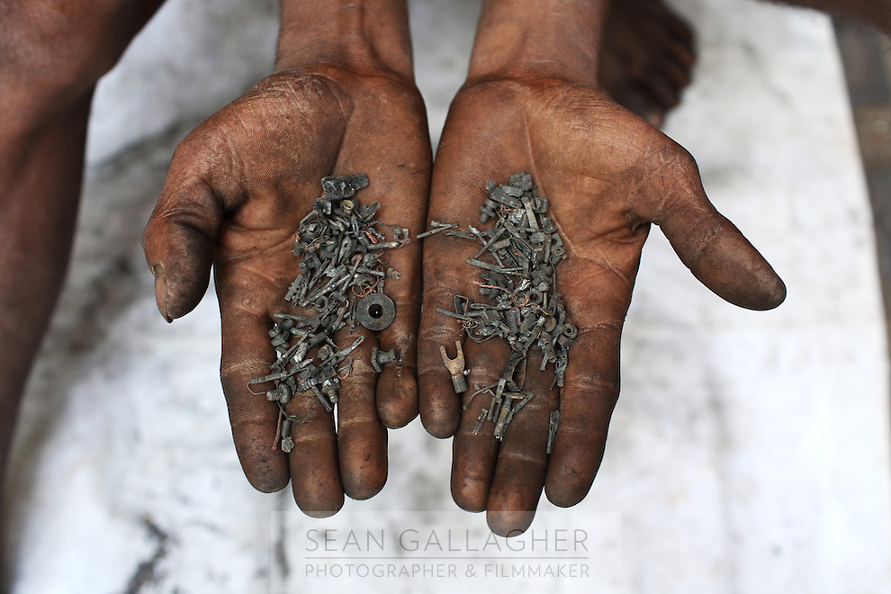 A man collects and sorts through small pieces of metal in the Chandni Chowk electronics market in central Kolkata. India. November, 2013