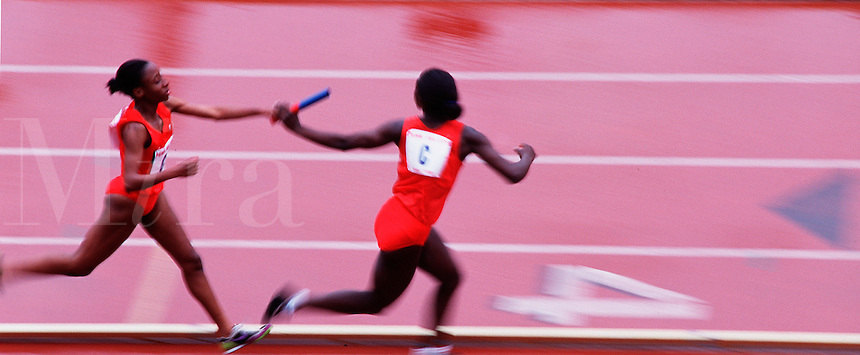 Blurred action image of female relay runners with a baton at a track meet.