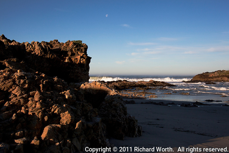 A gibbous moon hovers over the craggy, rocky beach at Pescadero State Beach on California's coast south of San Francisco.