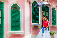 Young Chinese woman with an umbrella, posing for photoshoot in front of the old, colorful houses of Travessa da Paixao, in Macao China