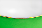 Green cup rim with gold leaf and white interior.  Macro close up.