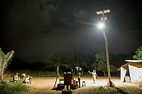A solar powered street light illuminates people selling food stuffs from roadside stalls.