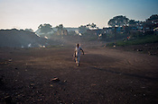 A resident walks past abandoned homes where smoke and methane gas billows out of the ground in Bokapahari village in Jharia, outside of Dhanbad in Jharkhand, India.   Photo: Sanjit Das/Panos