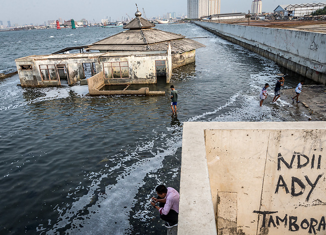15 August 2019, Jakarta, Indonesia: Local residents play on the shore in front of a mosque that has been claimed by the sea beside the protective seawall barrier at Muara Baru, North Jakarta built by the Government to keep the ocean from encroaching through the sinking city. The city is sinking at such an alarming rate the Federal Government is planning to move the capital off the island of Java to alleviate some of the strain that is causing the city to sink so quickly such as the draining of the groundwater table. Picture by Graham Crouch/The Australian