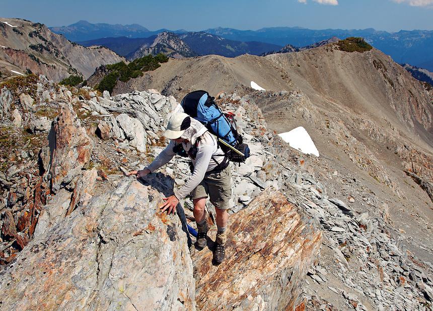 Backpacker scrambling up rock ridge, Bailey Range Traverse, Olympic Mountains, Washington