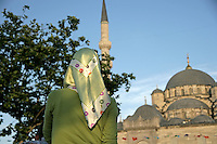 Back of Turkish girl in headscarf and the New Mosque, Istanbul, Turkey