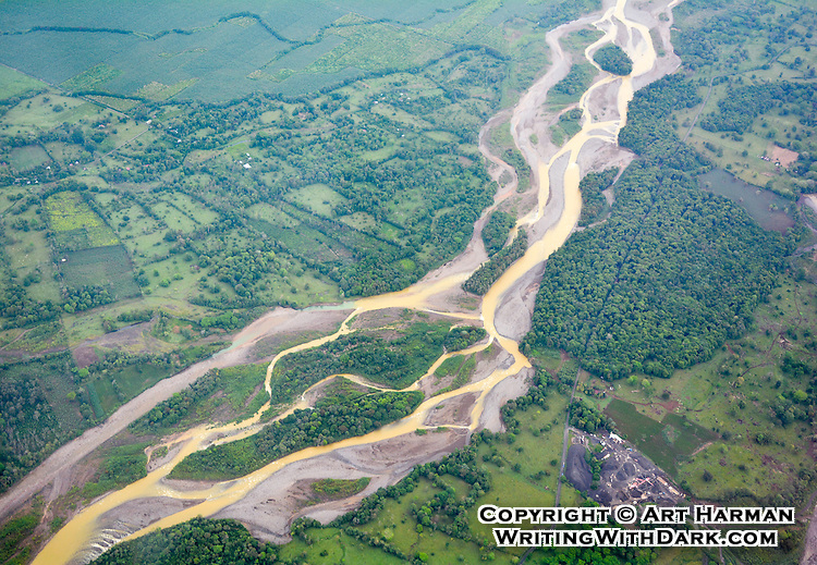 Flying low over a wild raging river in the spring in central Costa Rica