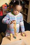 Education Preschool toddler 2s program girl building tower with small alphabet blocks