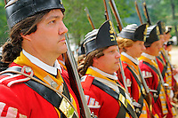 British redcoat soldiers of the Tenth Regiment of Foot stand to attention at a Revolutionary War encampment, Old Sturbridge Village, Massachusetts, USA.