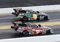 Sep 14, 2014; Concord, NC, USA; NHRA funny car driver John Force (top) defeats daughter Courtney Force during the Carolina Nationals at zMax Dragway. Mandatory Credit: Mark J. Rebilas-USA TODAY Sports