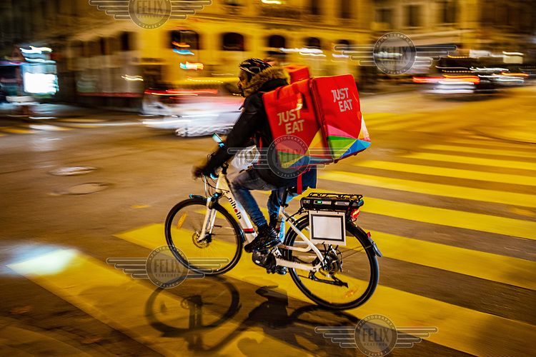A Just Eat delivery man rides a bicycle along the Rue de Berne, in Geneva's multi-cultural Paquis district during the second wave of the COVID-19 pandemic which saw restaurants and non-essential shops forced to close.