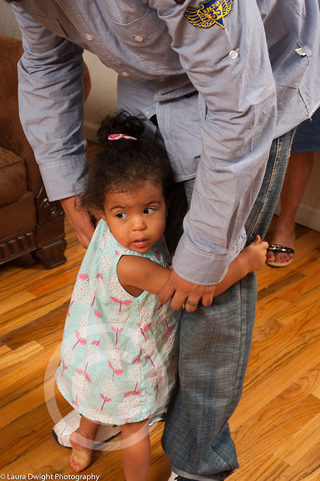 14 month old toddler girl turing to cling to father in new situation, shy